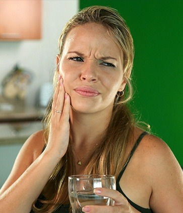 Woman in pain holding cheek before restorative dentistry