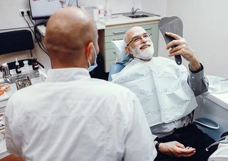A male patient looking at his smile in the mirror at the dentist's office