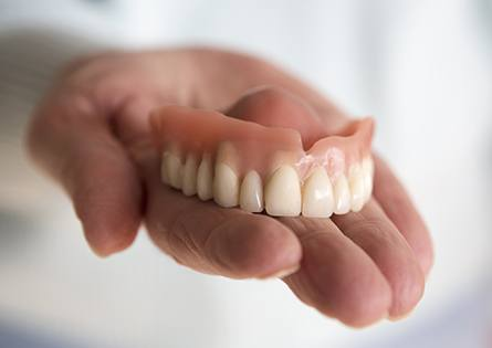 Hand holding full denture