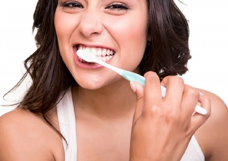 attractive woman smiling brushing teeth to care for porcelain veneers