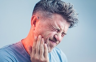 Man holding cheek in pain in need of restorative dentistry