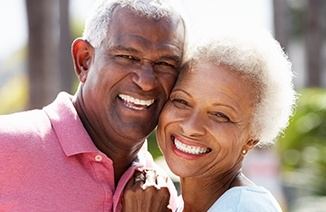 Older man and woman outdoors with healthy smiles after periodontal therapy