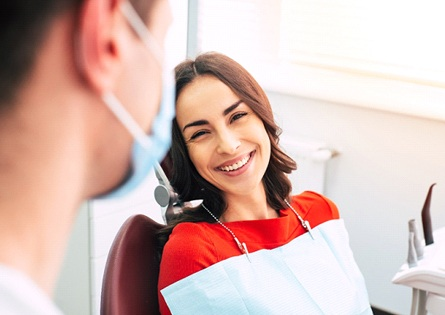 Woman smiling at dentist during teeth whitening appointment