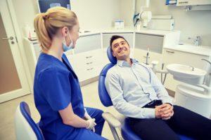 man in blue dress shirt smiling in dental chair