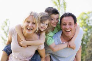 Parents and kids smiling together after visiting family dentist